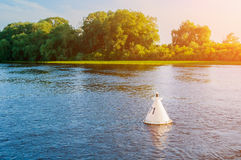 Paisaje de la puesta del sol del agua del verano - los árboles a lo largo del banco del río y de la boya en el agua bajo puesta d Imagenes de archivo