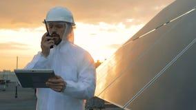 Paisaje de la puesta del sol en un tejado con un experto masculino que habla en un transmisor al lado de una batería solar metrajes