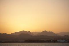 Paisaje de la puesta del sol - mar, montañas, cielo amarillo Fotografía de archivo