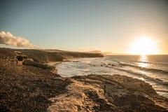 Paisaje de la puesta del sol del océano con la costa costa Fotos de archivo libres de regalías