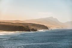 Paisaje de la puesta del sol del océano con la costa costa montañosa y las olas oceánicas azules Fotografía de archivo