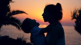 Paisaje de la puesta del sol y una mujer que engaña alrededor con su niño Madre y ni?o almacen de metraje de vídeo