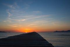 Paisaje de la salida del sol con la pequeña silueta humana Foto de archivo