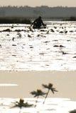 Paisaje de la salida del sol con un hombre pesquero en el lago africano imagen de archivo