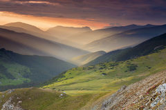 Paisaje de la salida del sol del verano en las montañas de Cárpatos, en el camino de la montaña de Transalpina Imagen de archivo