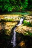 Paisaje de la selva con agua de la turquesa que fluye de la cascada georgiana de la cascada en la montaña de color verde oscuro d imágenes de archivo libres de regalías