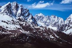 Paisaje de las montañas de la nieve contra el cielo azul Foto de archivo