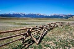Paisaje de montañas rocosas con la cerca del registro Fotografía de archivo