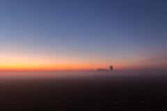 Paisaje de niebla industrial, silueta de la fábrica vieja contra el cielo de la puesta del sol y la niebla en la hora azul en la  Fotos de archivo libres de regalías