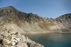 Paisaje del alto del lago de la montaña en las montañas de Dombai El circo formó por un glaciar con un lago profundo y un agua az imágenes de archivo libres de regalías