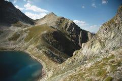 Paisaje del alto del lago de la montaña en las montañas de Dombai El circo formó por un glaciar con un lago profundo y un agua az imagen de archivo libre de regalías