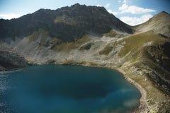 Paisaje del alto del lago de la montaña en las montañas de Dombai El circo formó por un glaciar con un lago profundo y un agua az foto de archivo