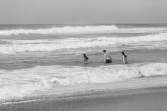 Paisaje del blanco del negro de la playa del océano de la nadada del muchacho de las muchachas Foto de archivo libre de regalías