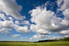 Paisaje del campo con el cielo nublado azul imagen de archivo