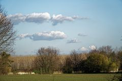 Paisaje del campo de la agricultura, tierra vacía, cielo azul y nubes en primavera Foto de archivo