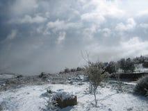Paisaje del campo - nieve en invierno y nubes oscuras Imagen de archivo