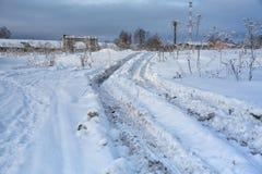 Paisaje del campo Rastros de neumáticos del tractor en nieve Fu profundo Foto de archivo