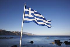 Paisaje del Cretan con la bandera griega y el mar libio Imágenes de archivo libres de regalías