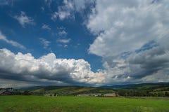 Paisaje del día de verano con el campo, el cielo nublado y el pueblo Foto de archivo