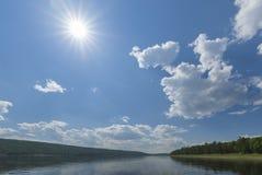 Paisaje del día de verano con el río, el bosque, las nubes en el cielo azul y el sol Fotos de archivo