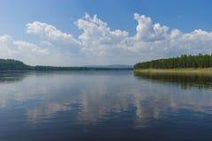 Paisaje del día de verano con el río, el bosque, las nubes en el cielo azul y el sol Foto de archivo