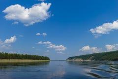 Paisaje del día de verano con el río, el bosque, las nubes en el cielo azul y el sol Imagen de archivo