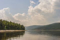 Paisaje del día de verano con el río, el bosque, las nubes en el cielo azul y el sol Foto de archivo libre de regalías