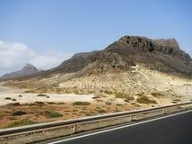 Paisaje del desierto con las montañas y el camino de la pista de despeque Foto de archivo