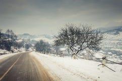 Paisaje del invierno, camino nevado en las montañas con los árboles Imágenes de archivo libres de regalías
