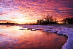 Paisaje del invierno con el lago y el cielo ardiente de la puesta del sol. Imagen de archivo