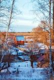 Paisaje del invierno con el pueblo ruso Nevado en la puesta del sol Foto de archivo