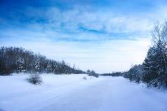 Paisaje del invierno con el río congelado y el cielo azul imagen de archivo