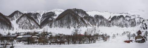 Paisaje del invierno con las montañas y el pueblo viejo Imagen de archivo libre de regalías