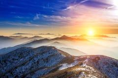 Paisaje del invierno con puesta del sol y de niebla en las montañas de Deogyusan Foto de archivo