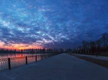 Paisaje del invierno con puesta del sol nublada sobre el lago congelado fotos de archivo libres de regalías