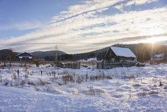 Paisaje del invierno con un pueblo abandonado en la puesta del sol Imagen de archivo