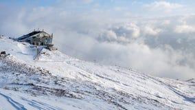 Paisaje del invierno con una casa en la montaña con neblina y nieve fotografía de archivo libre de regalías