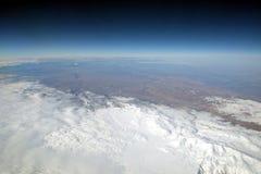 Paisaje del invierno de las montañas de la nieve del avión en estratosfera con el cielo azul marino foto de archivo