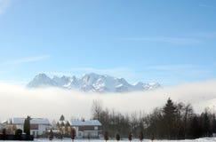 Paisaje del invierno en la madrugada en Austria con nieve, los edificios de madera, el cielo azul y el espacio de la copia Foto de archivo