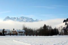 Paisaje del invierno en la madrugada en Austria con nieve, los edificios de madera, el cielo azul y el espacio de la copia Imagen de archivo libre de regalías