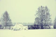 Paisaje del invierno en un día embotado frío con el pajar Fotos de archivo