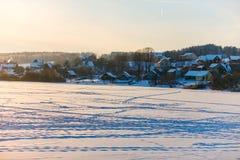 Paisaje del invierno Lago congelado cubierto con nieve Vida en pueblo imagen de archivo