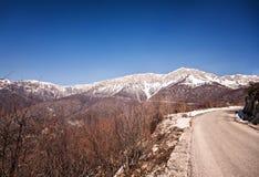 Paisaje del invierno que muestra la montaña rocosa y el camino Imagen de archivo libre de regalías
