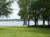 Paisaje del lago con la estatua de piedra fotos de archivo