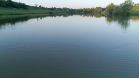 Paisaje del lago de la tarde, lago limpio entre árboles verdes contra el cielo en la posluminiscencia almacen de video