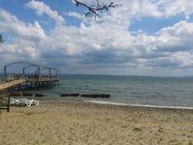 paisaje del mar con el muelle del cielo nublado y de madera Imagen de archivo
