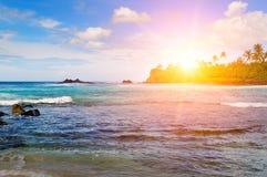 Paisaje del mar con la isla rocosa y la salida del sol Playa Fotos de archivo