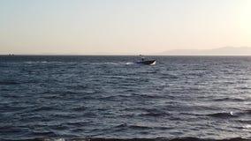 Paisaje del mar de la cámara lenta con un barco que mueve encendido el mar almacen de metraje de vídeo