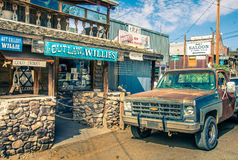 Paisaje del oeste salvaje moderno con las tiendas del turista y el coche oxidado viejo de la recogida en Oatman Imagenes de archivo
