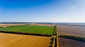 Paisaje del otoño: cielo azul, árboles coloridos, campos amarillos Foto de archivo libre de regalías
